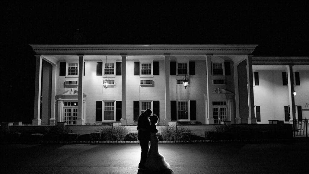 Black and white bride and groom infront of the Drexelbrook Mansion