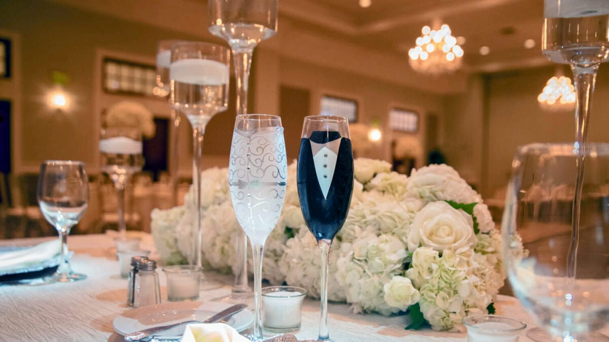 Bride and Groom decorated Champagne Flutes placed at the sweetheart table in the Drexelbrook Grand Ballroom