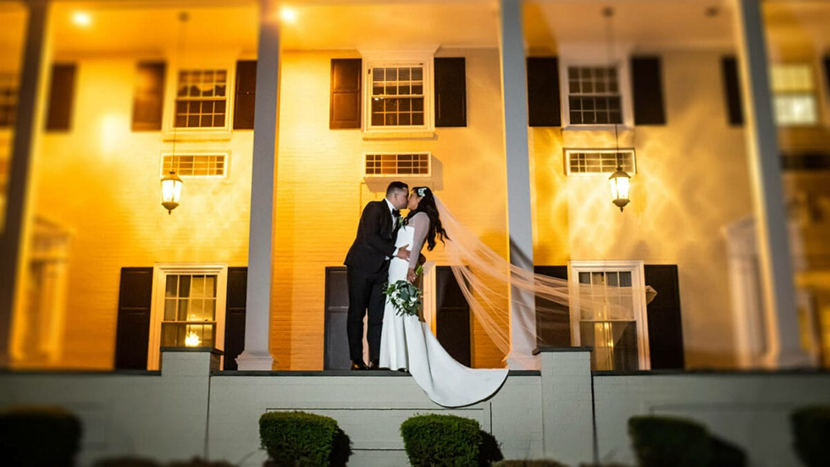 Couple Standing on Patio in Front of Drexelbrook Mansion at Night