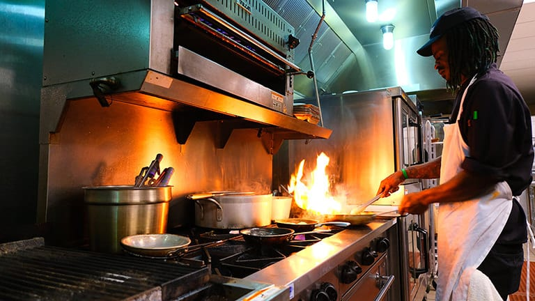 Sous Chef preps meal over flame in kitchen
